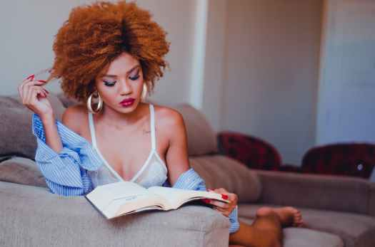 woman reading book on gray sofa